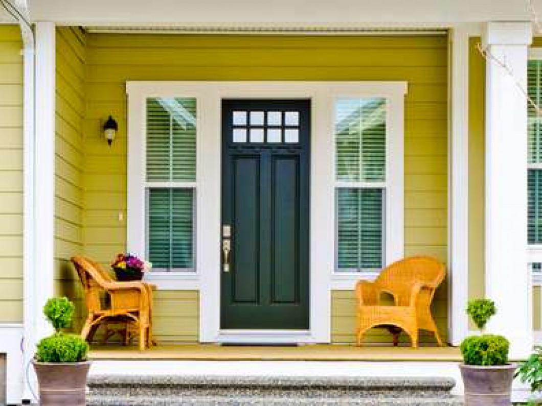 dark wooden door with light yellowish-green siding and white trim